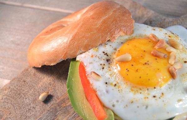 Bagel met een gebakken eitje, avocado en paprika